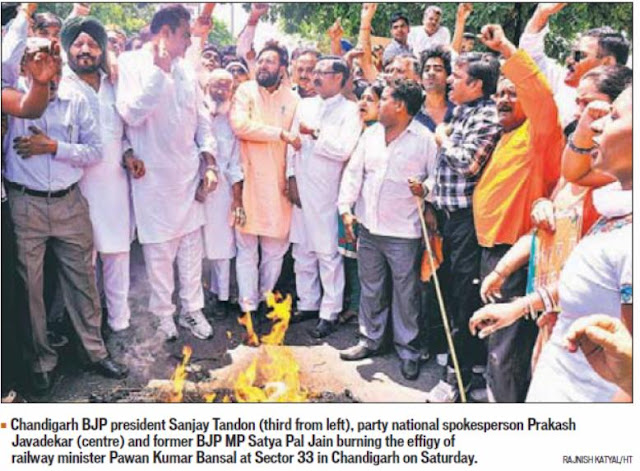 National spokesperson Prakash Javadekar and former BJP Satya Pal Jain buring the effigy of railway minister Pawan Bansal at Sector 33 in Chandigarh on Saturday.