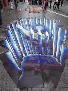 3 D Kreide Kunstwerk von Udo Lindenthal aus Deutschland. Abgrund Blaue Hand hält eine Kristallkugel