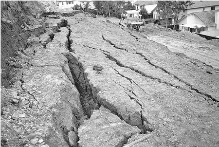 Slope failure during the grading of a site. The backpack located in the middle of the photograph provides a scale for the size of the ground crack