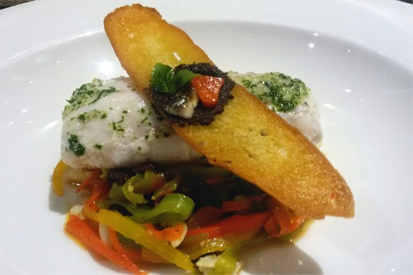 Hake fillet with squid, peppers and olives.