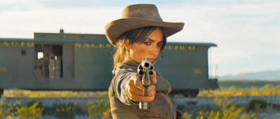 Penelope Cruz locked and loaded with a six shooter pointed at the camera.