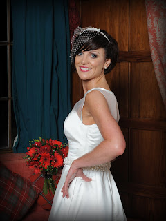 Scottish bride in a white dress with red bouquet in a hotel wedding venue in scotland