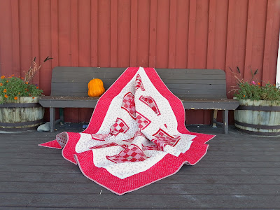 a red and white quilt cascading over a wooden bench
