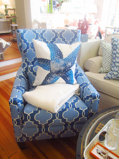 dark and light blue patterned arm chair with a white pillow with a blue starfish printed on it