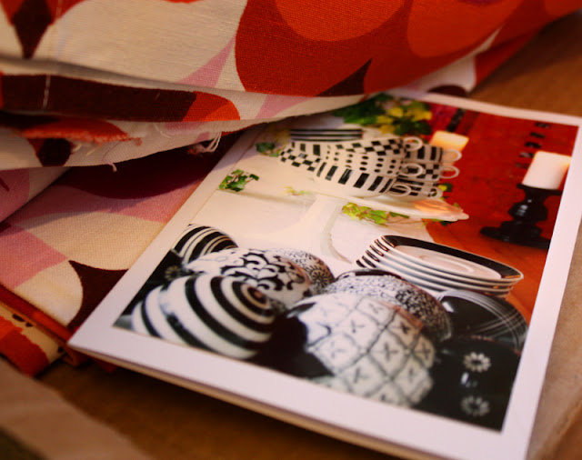 bunter Stoff in Päckchen Farben weiß, braun, pink, rosa, orange, rot, mit Karte, Fotografie Kugeln schwarz weißer Dekor, Tassen Untertassen in schwarz weiß