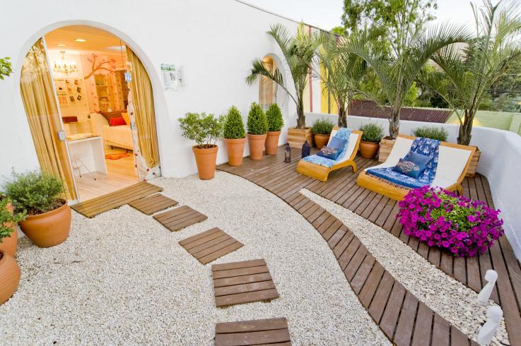 deck em jardim pequeno:Composição de topiarias, palmeiras e flores.