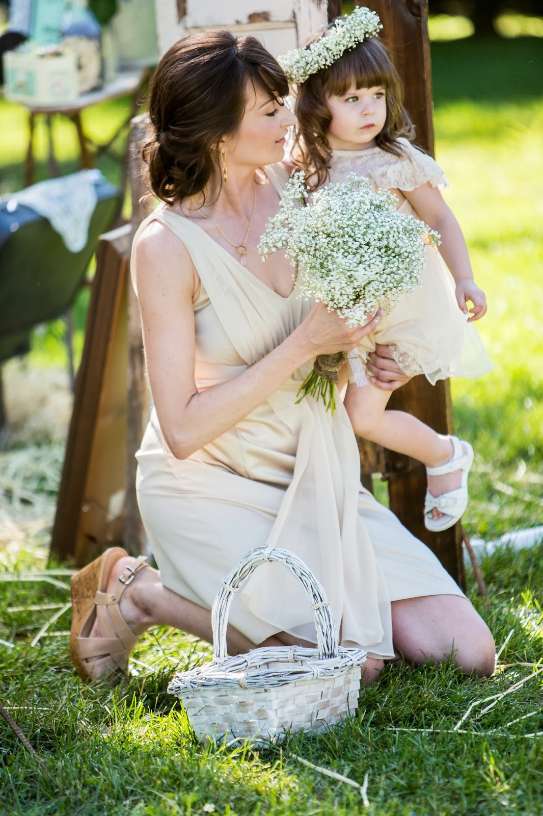 bridesmaid holding flower girl and a bouquet of flowers
