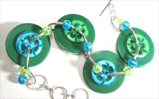Bold bracelet has big green buttons and teal flower buttons accented with shiny beads