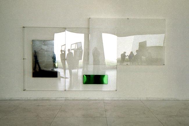 Parede com espelhos não completamente planos, originando imagens distorcidas do ambiente da sala