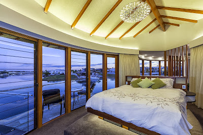 luxurious master bedroom having contemporary design with its ship-shapped ceiling and open to the beach view