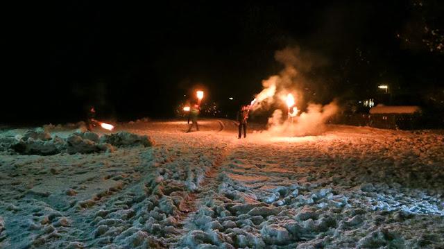 Osterfeuer mit Fackelschein im Schnee
