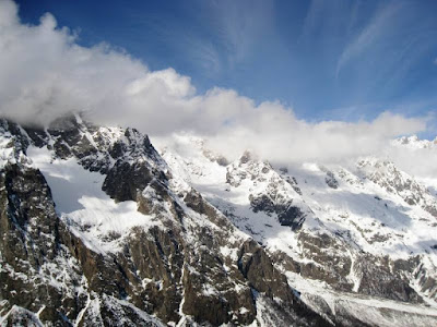Blue skies and fluffy cloud over snowy peaks