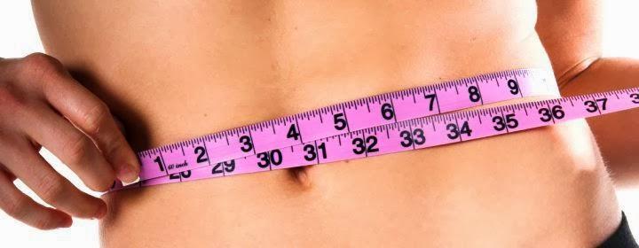 Mulher com fita métrica medindo a cintura