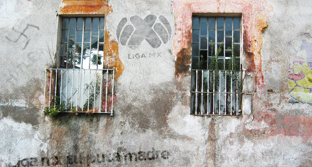 Pared grafiteada de una casa abandonada con los vidrios de las ventajas rotos y sucios | Ximinia
