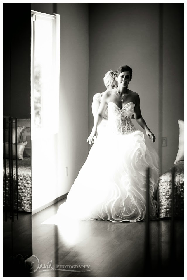 black and white shot of bride getting into her gown