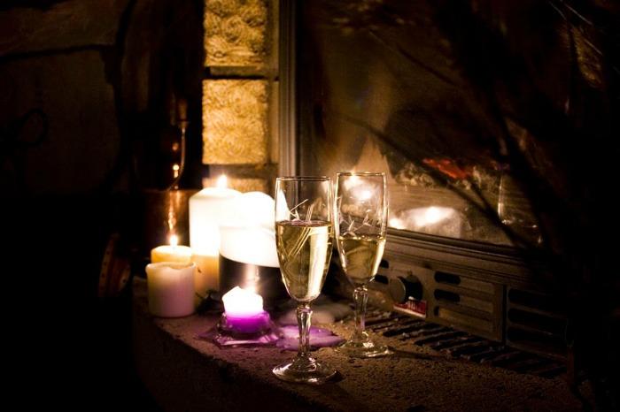 sobremesa romántica junto a la chimenea con flores, cava, velas, dulces