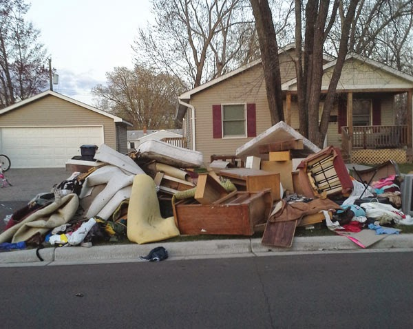 curbside clean up with large pile of mattress, carpet and stuff
