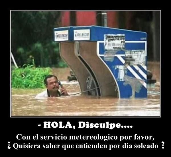 Un hombre en una inundacion llamando por una cabina telefinica.