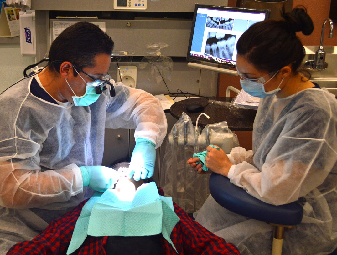 image of dental clinic students providing service to a young patient.