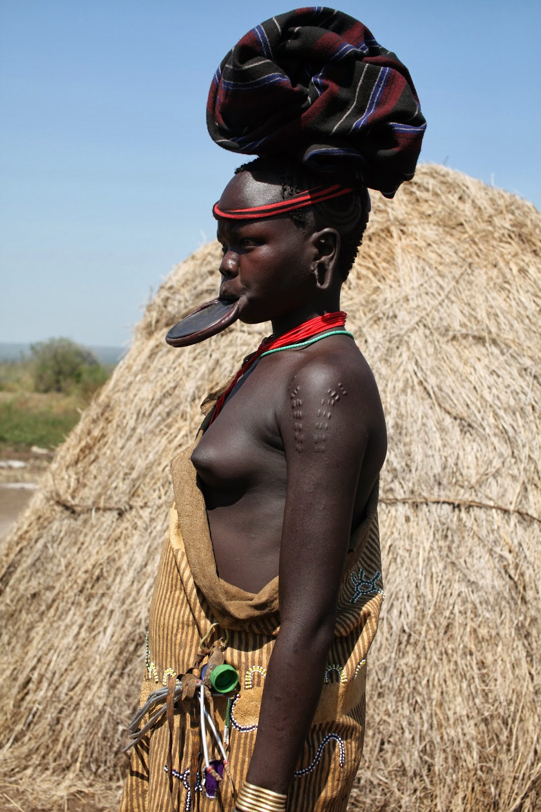 Profile of Young Mursi Girl showing Lip Plate, Body Scarification and the bangles made from brass bullet casings