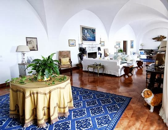 Living room in Castiglione castle in Capri with blue and white rug, white sofa, arches and terra cotta tile floor