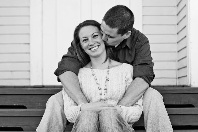 couple snuggling on steps of old schoolhouse