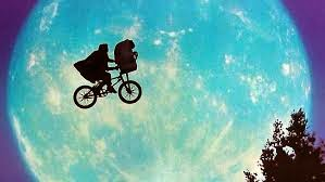 Silhouette of cyclist and the character E.T. against the moon.