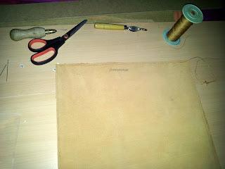 Petit espace de travail du cuir avec poinçon, aiguilles, fil, roulette de marquage
