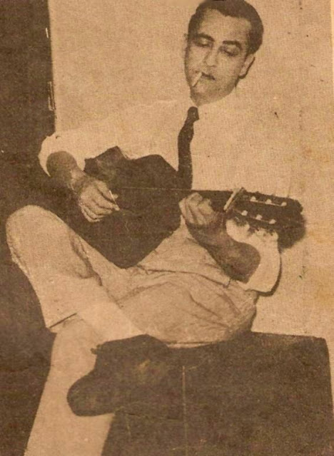 Hugo del Carril tocando la guitarra con un pucho en la boca
