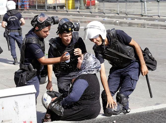 Полицейские помогают промыть глаза женщине, пострадавшей от слезоточивого газа в Анкаре, Турция, в 2013 году.