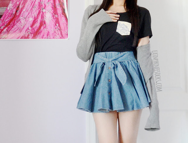 A casual, simple everyday outfit with the Japanese Village pocket tee from Tea Apparel, a gray cardigan, and a blue tie-front denim skater skirt.