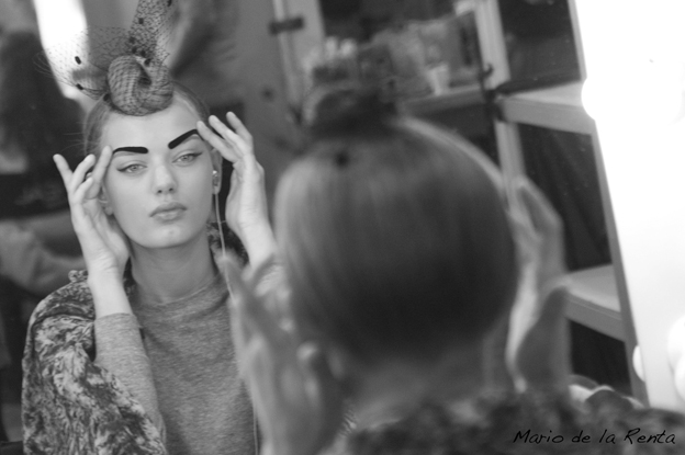 Model looking her reflection on a mirror before a fashion show