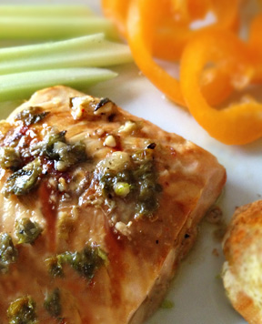 Image of plate with salmon, lemon caper sauce is on top.