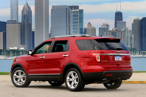 Rear 3/4 view of red 2011 Ford Explorer with Chicago skyline in background