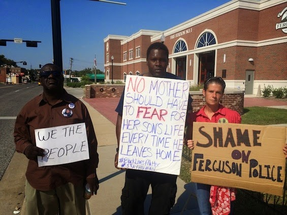 Photo Credit - Riverfront Times - Protesters hold signs in support of Murdered Ferguson, MO Resident Mike Brown