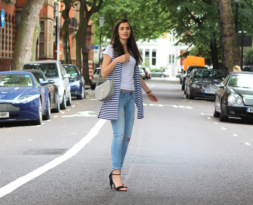 peexo fashion blogger wearing white tshirt and ripped jeans and strappy heels and striped sleeveless vest