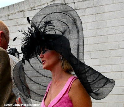 a women at the track wearing a huge black hat with see through netting in rings tilted on one side of her head with sprigs of black feathers coming out of the center and wearing a bright pink dress