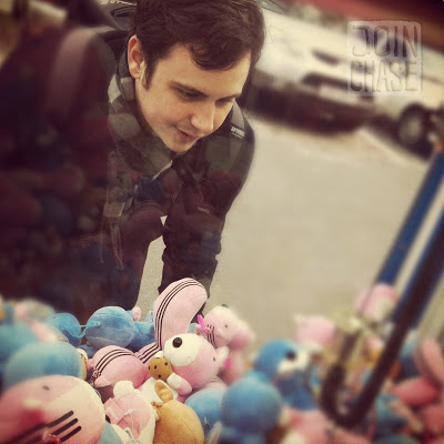 A foreign man playing a claw machine in Seoul, South Korea.