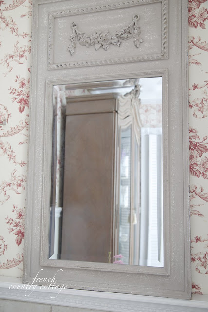 Gray mirror in bathroom with red toile wallpaper