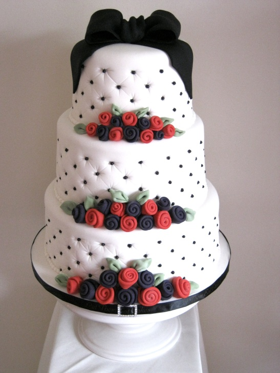 A wedding cake to the bride 39s design with black deep purple and red as the