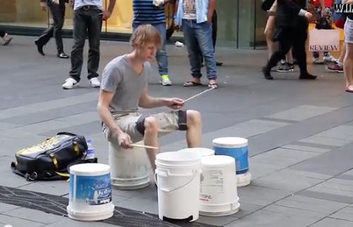 Baterista dá show impressionante com baldes no meio da rua