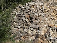 Mur de pedres granítiques per evitar el desplom del talús del camí