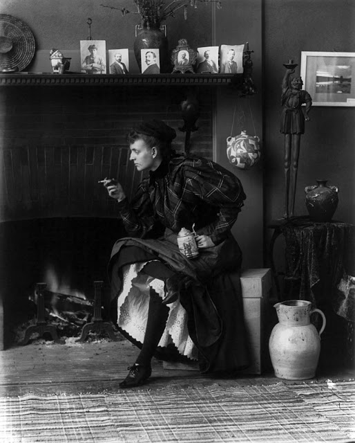 Frances Benjamin Johnston, full-length [self-]portrait, seated in front of fireplace, facing left, holding cigarette in one hand and a beer stein in the other, in her Washington, D.C. studio, 1896.