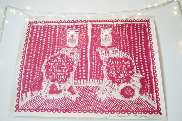 Signed Rob Ryan print on wall with fairy lights