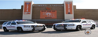 Two University police cars parked in front of  Bower's Stadum