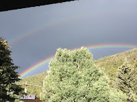 photo by Katy Manck of  Colorado double rainbow in dark cloudy sky