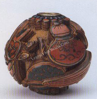 """A lacquer ojime made of at least 19 yellow, black, and red layers of lacquer Carved in relief, it depicts symbols of Japan's aesthetic life, including tea ceremony implements, musical instruments, and a basket of fruit culled """"Buddha's hand.""""Diameter, 1. 6.5 cm."""