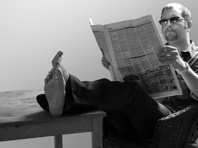 Image of a middle aged confident man enjoying himself reading a paper in the power pose