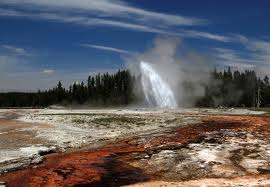 Foreground, wierd colours of dried chemical deposts on the shore of a lake or pond, middle ground erupting water geyser, background pine trees.