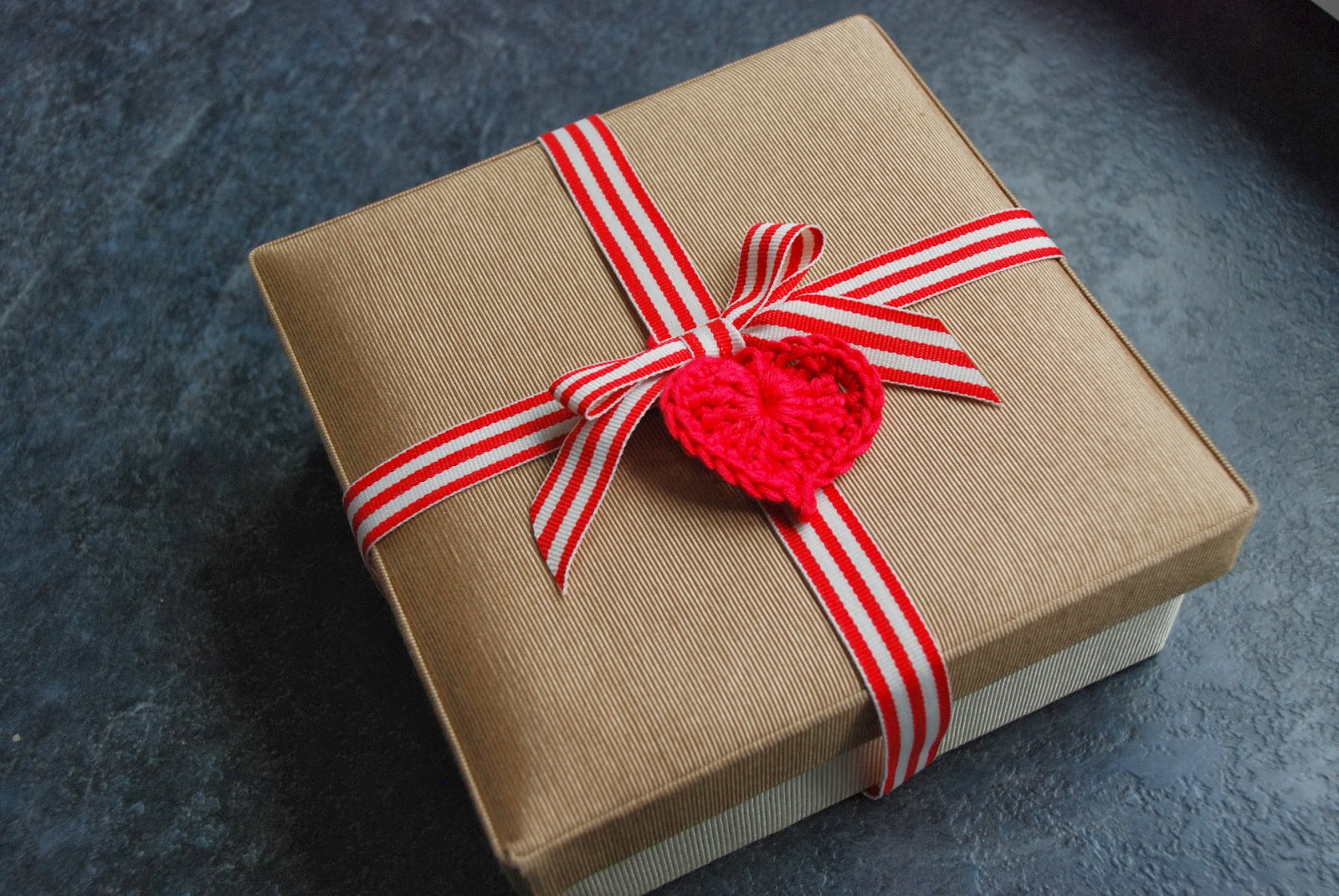 image of gift box tied with ribbon and a crochet heart